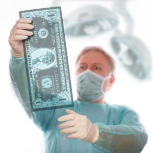 A surgeon holds up an x-ray of money